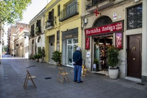 A man waits his turn outside a pharmacy in Barcelona