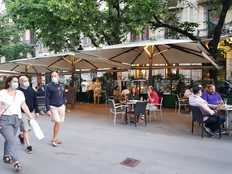 Tables spaced at 2-metres apart in the Rambla de Catalunya, with people walking wearing face masks on 25 May 2020.