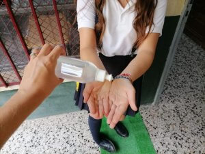 A pupil using hand sanitiser
