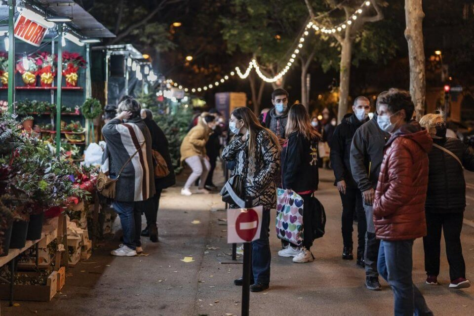 People wearing face masks and queuing to shop at the Sagrada Familia Christmas Market