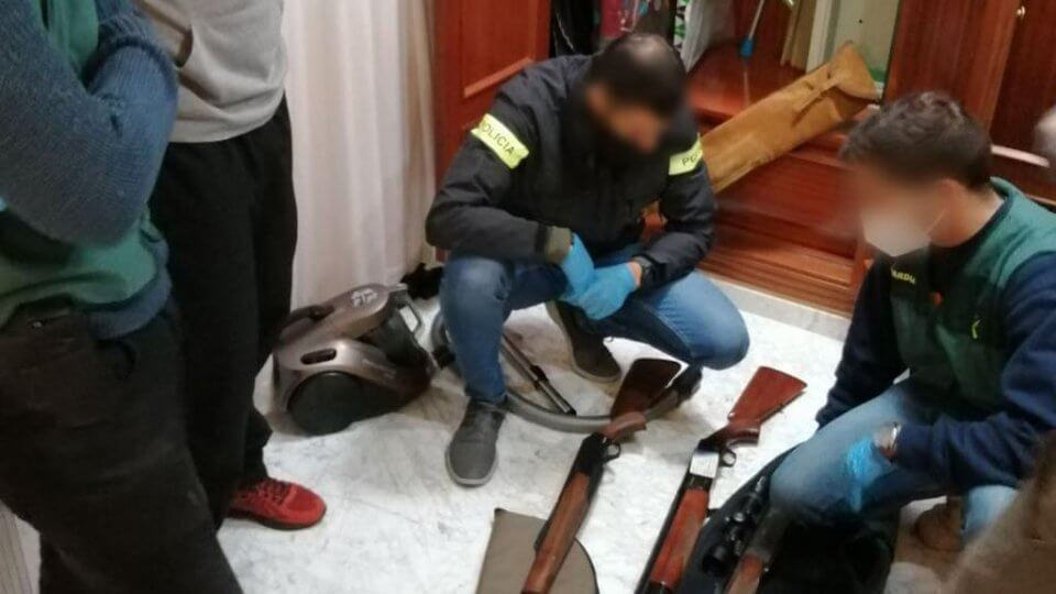 An image of the police inspecting weapons found