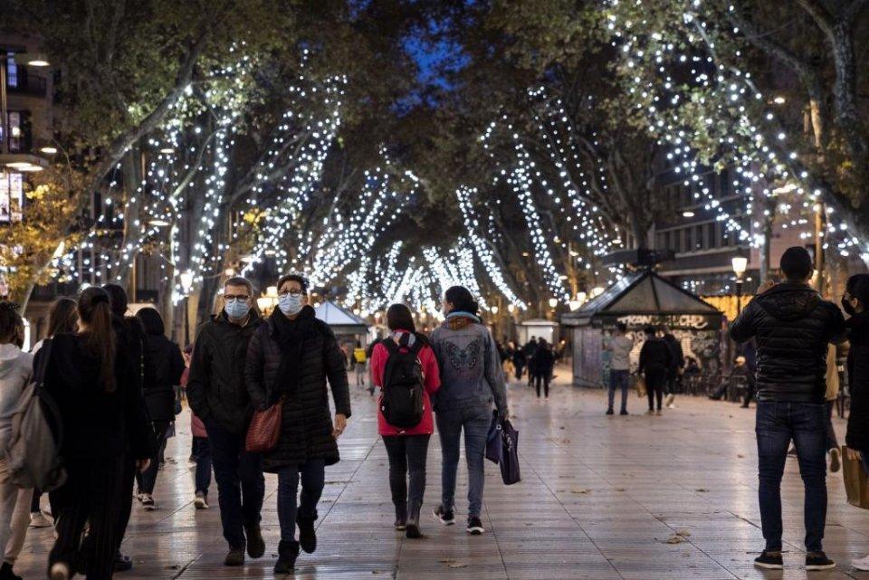 People with face masks walking along La Rambla boulevard in central Barcelona