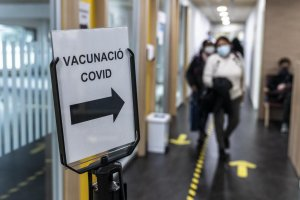 A sign in Catalan indicating the way for Covid vaccinations for essential and home care workers