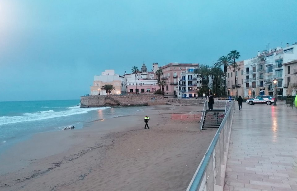 Police on Sant Sebastian beach in Sitges, where the dead dolphin was found.