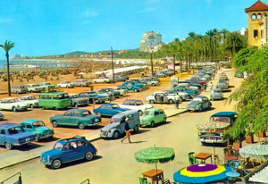 Old postcard image of cars parked near La Fragata beach in Sitges.