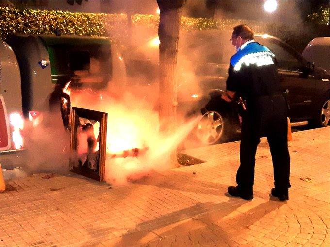 A local police officer extinguishing a fire in rubbish container In Sitges