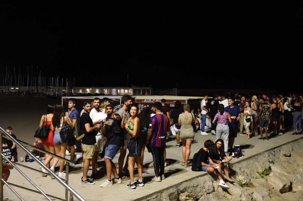 Young people gathering on the breakwater at Fragata beach in Sitges.