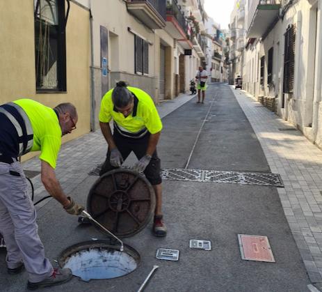 Two workers disinfecting drains in the Carrer de l'Estalvi.